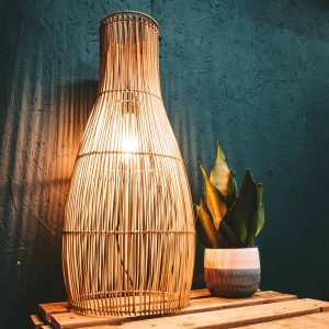 Rattan Lampshade Lantern with light in dark on table with plant